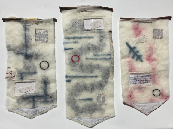 three felted collages hanging from sticks