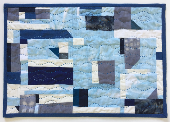 small randomly pieced quilt with wavy embroidered quilting and embroidered outlines of eyes