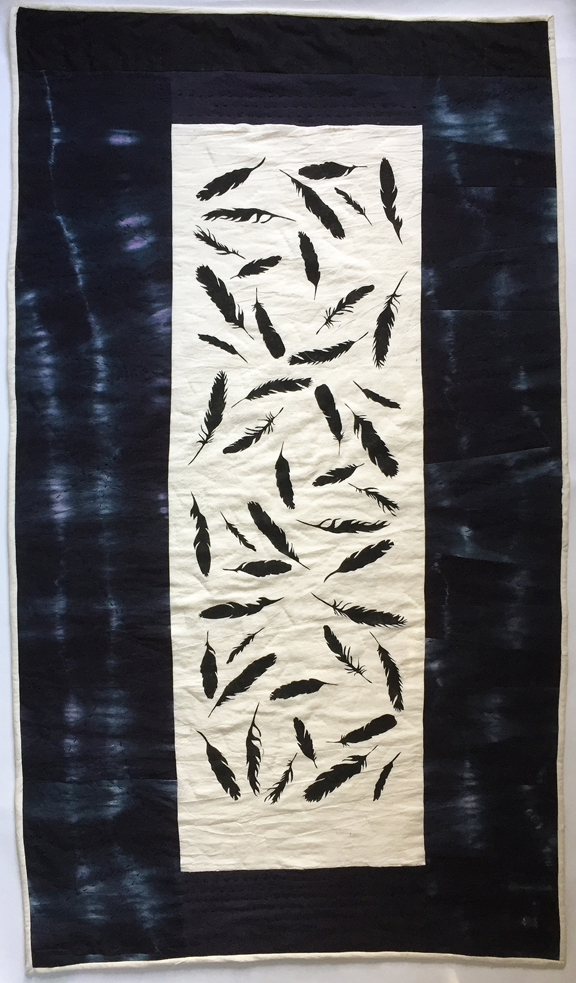 quilt with stenciled crow feathers and night fabric