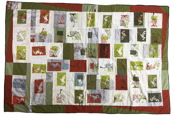 block quilt with various prints of trees and people