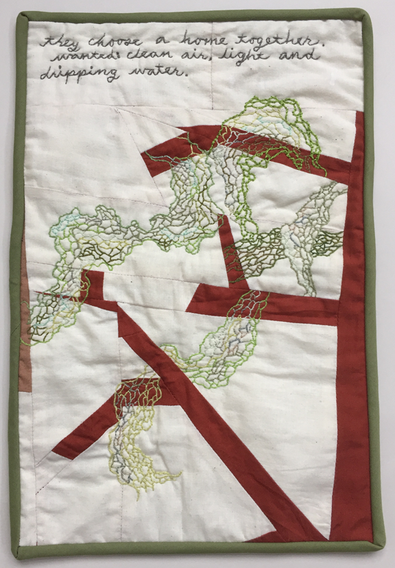 quilt with embroidered lace lichen hanging from tree