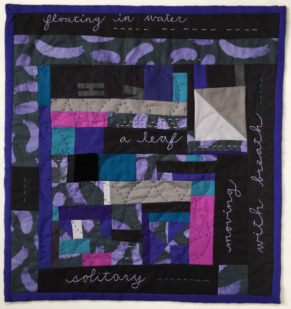 small randomly pieced quilt with embroidered text and sewn crossed circles with leaflike pattern